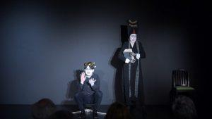 Szene aus Leonce und Lena. Prince Leonce sitz mit einem goldenen Lorbeerkranz auf einem Hocker. Neben ihm steht die Hofadame mit einem Stapel Bücher in der Hand.