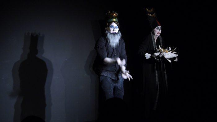Auf schwarzer Bühne steht links König Peter mit einem grauen langen Bart und seiner Krone. Er führt sonderbare Handgebärden aus. Recht von ihm steht die Hopfdame mit dem weißen Krönungskissen in der Hand.