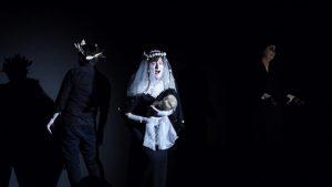 Schauspielerin mit Hochzeitsschleier hält Babypuppe vor sich.