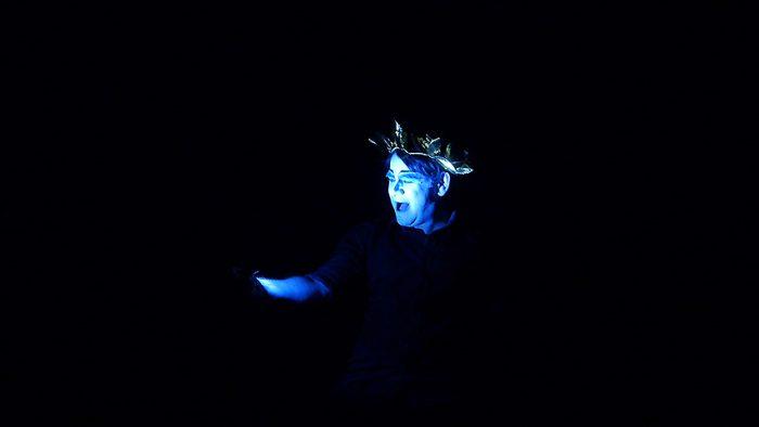 Schauspieler sieht sich selbst in blauem Licht vor schwarzem Hintergrund.