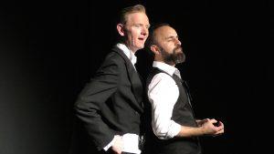 Auf der Bühne, links ein Mann in einem Frack, er wirkt sehr britisch, schaut mit offenen Augen ins Publikum. Rechts von ihm steht sehr nah ein orientalisch aussehender Mann mit Bart. Er hat die Augen geschlossen und stellt sich gerade etwas vor.