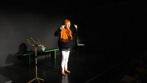 Eine Frau steht auf der Bühne. Sie trägt eine enge weiße Hose, einen schwarzen Pulli und einen orangenen Schal. Der passt prima zu ihren orangefarbenem Haaren. Sie zeigt eine Schläfenschraube. Christa Brunhuber trägt etwas zum Thema Heimat vor.