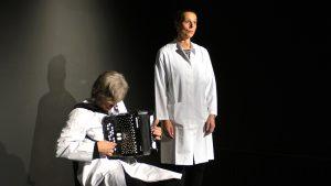 Ein Mann sitzt und rechts von ihm steht eine Frau. Beide tragen einen weißen Laborkittel. Es sind zwei Musiker, die auf der Bühnen Labormusik spielen. Er spielt Ziehharmonika und sie singt.