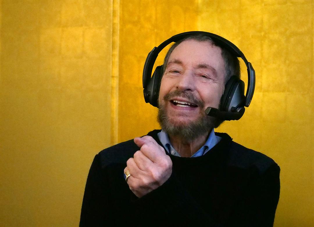 Wolfgang Keuter mit Headset vor goldenem Hintergund