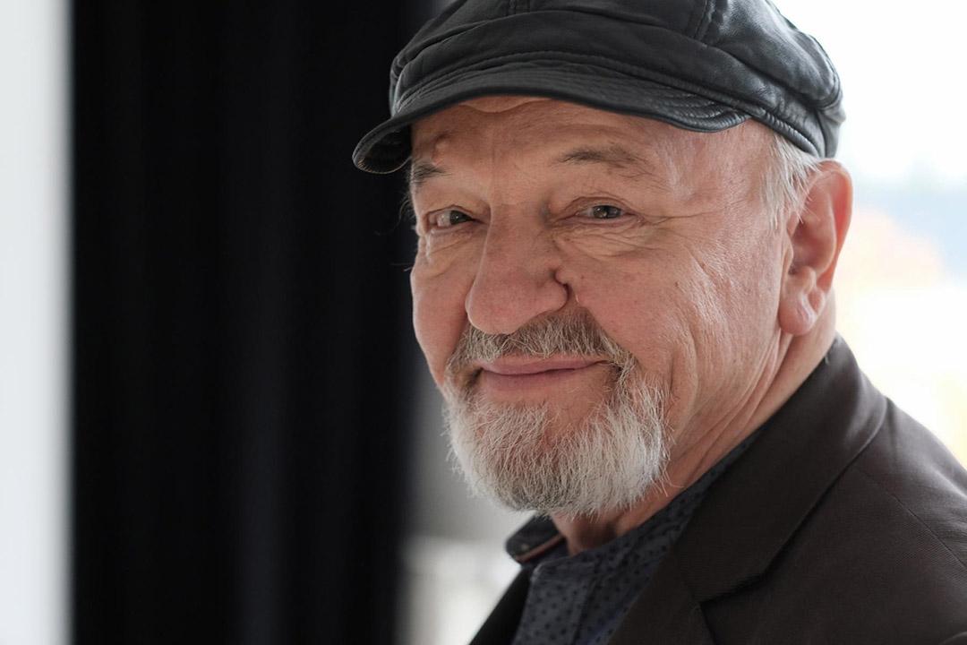 Der Schauspieler Walter Gontermann lächelt in die Kamera. Er Trägt eine dunkle Schiffermütze.