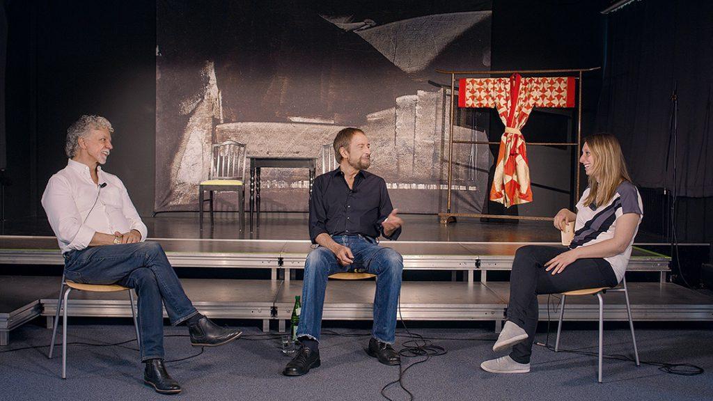 Vor der Bühne auf dem Campus Golzehim sitzen links Gianni Sarto, weißes Hemd und Jeans, in der Mitte wolfgang Keuter, scharzes Hemd und Jeans und rechts Katharina Gregori, weißes Shirt mit dunkler Hose