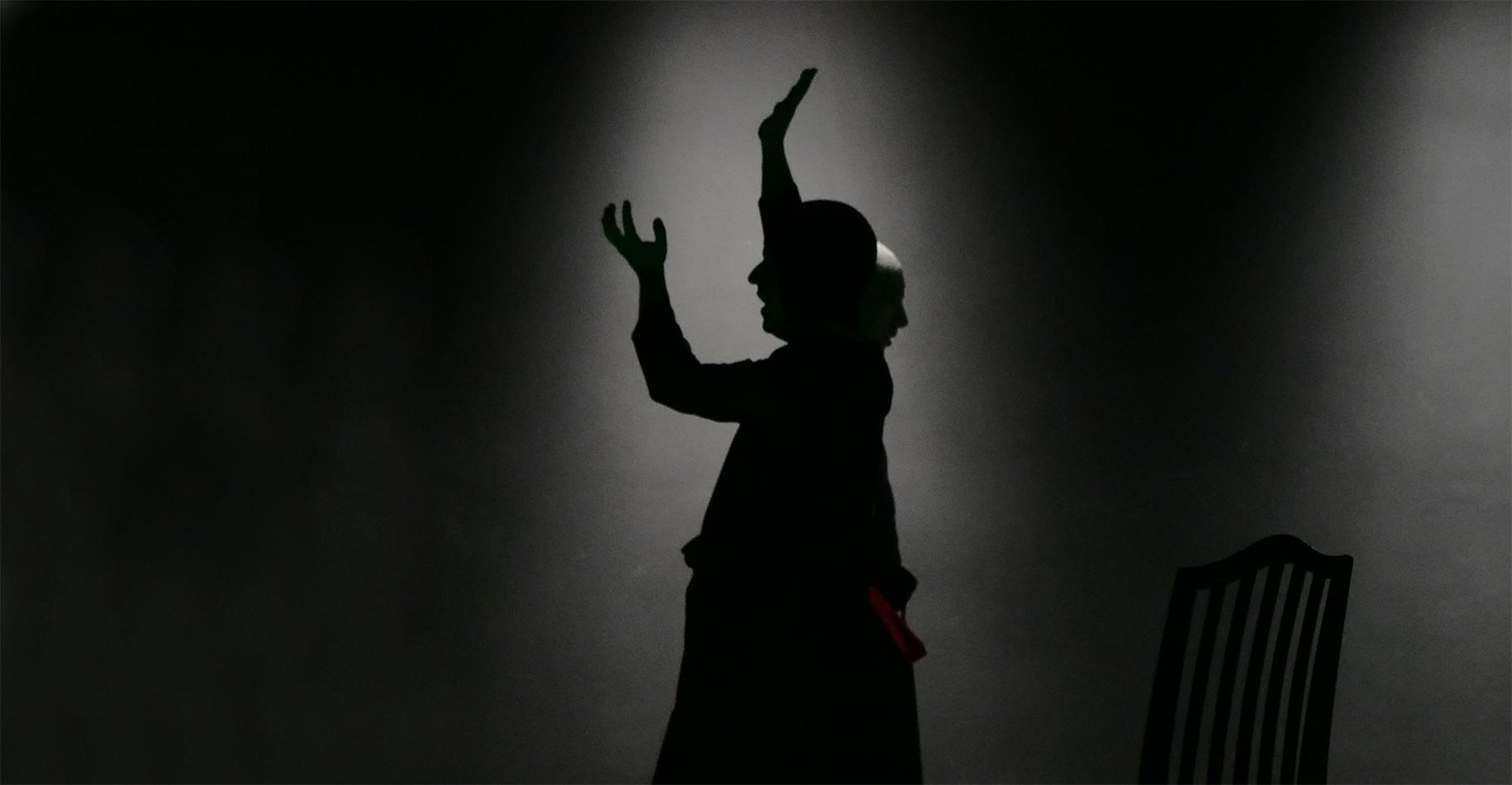 Probenfoto Wandlung21: Zwei Schauspieler im weiß beleuchtetem Bühnenraum. Sie zwigen starke Gebärden im Profil.