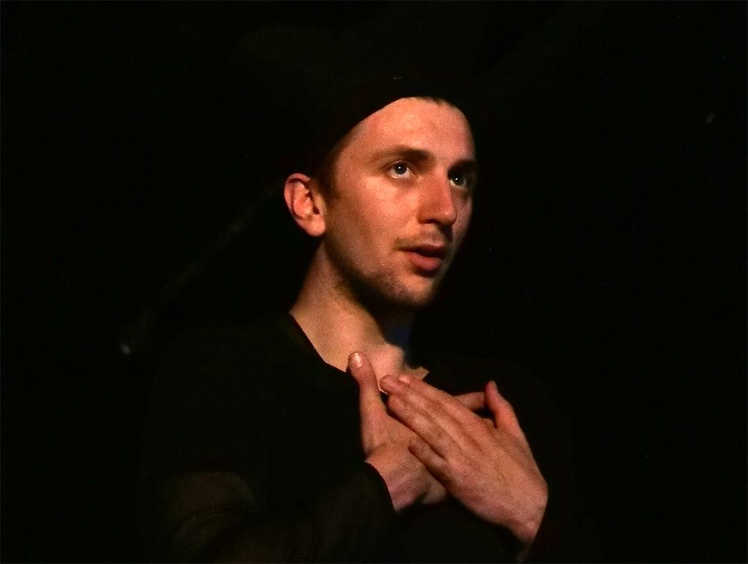 Probenfoto Wandlung21: Ein Schauspielerportrait im dunklen Bühnenraum. Er trägt schwarze Kleidung und hält die Hände übereinander vor dem Hals.