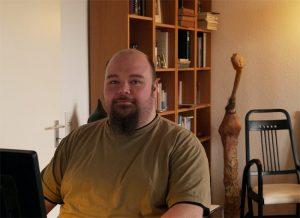 Ein Mann sitzt am Computer vor Bücherregalen in einem schönen Homeoffice