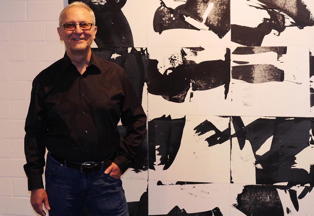 """Der Künstler Rolf Abendroth steht für seinem großen, schwarz-weiß Bild """"Reflections"""" im Bühnenraum des TheaterLabor TraumGesicht."""