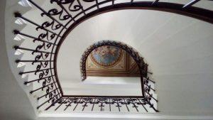 Treppenhaus mir bemalter Decke ud einer spiralförmigen Treppe in Meran, Obermais