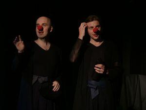 Probenfoto Wandlung21: Zwei Schauspieler im grün beleuchtetem Bühnenraum. Sie zwigen starke Gebärden im Profil.