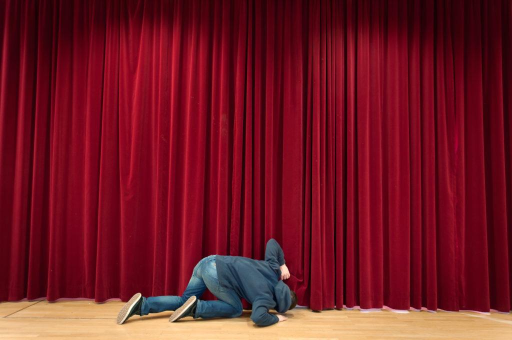 Mann steckt neugierig seinen Kopf unter Roten Theatervorhang