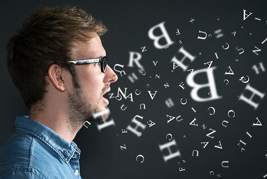 Links am Bildrand ist das Profil eines jungen Mannes mit Brille zu sehen. Auf dunklem Hintergrund fliegen überall Buchstaben im Raum