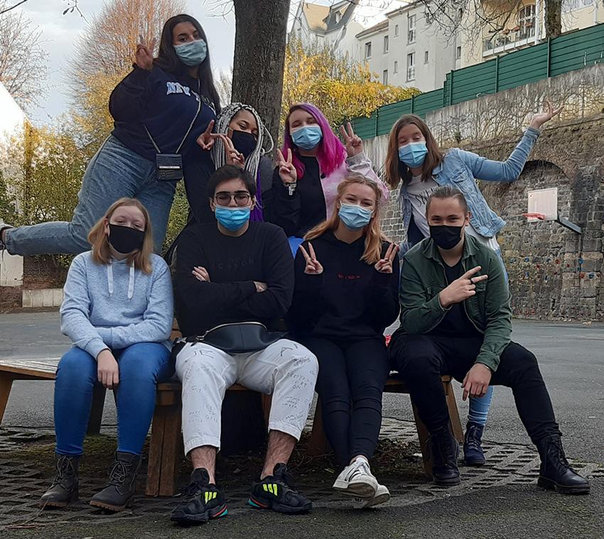 Gruppenfotos von 8 Schüler*Innen des KAbarettungsdienstes. Sie sitzen auf dem Schulhof vor einem Baum auf einer Bank. Alle tragen Coronamasken