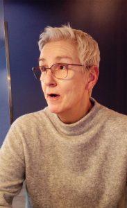 Antje, eine Frau mit kurzen weißen Haaren, shaut nach links. Sie hat einen erstaunten Gesichtsausdruck.chwarzem Rollo. Darauf steht ein Drucker. Sie trägt eine Brille und lacht in die Kamera.
