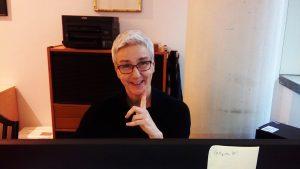 Antje, eine Frau sitzt vor einem Büroschrank mit schwarzem Rollo. Darauf steht ein Drucker. Sie trägt eine Brille und lacht in die Kamera.