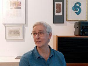 Eine Frau mit Brille sitzt in ihrem Büro. Sie trägt eine blaue Hemdbluse und eine dunkel umrandete Brille. Mit einem Lächeln schaut sie nach links. Im Hintergrund ein Drucker auf einem Büroschrank und unterschildliche Bilder. eines zeigt eine blaue, asiatische Kalligraphie.