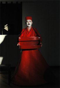 Ein Schauspieler in einem roten Gewand, ein riesiger roter Reifrock, ein asiatisches Hemd und ein runder roter und breiter Reif auf dem Kopf als eine Art Krone. Er ist stark asiatisch geschminkt und hat einen roten Bauchladen umhängen. Er zeigt den Streichholzverkäufer aus dem Stück: Ein leichter Schmerz von H. Pinter.