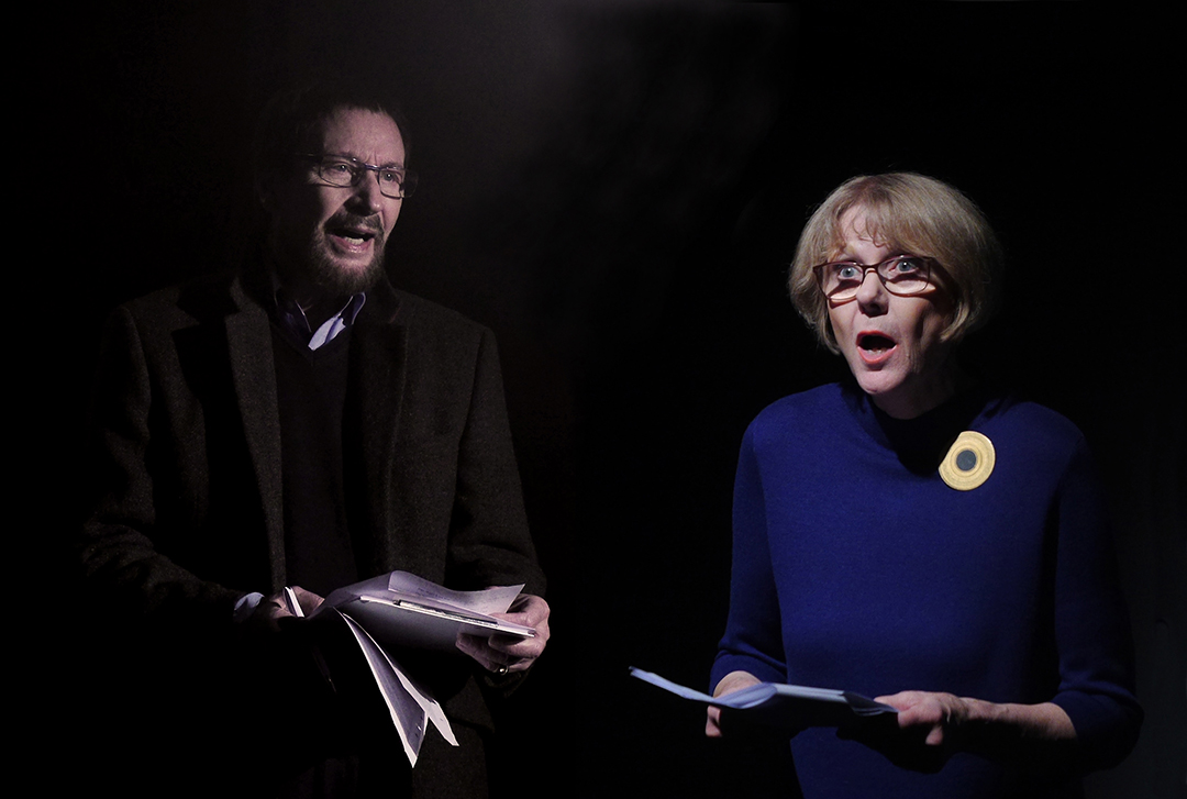 Im schwarzen Bühnenraum. Links steht Wolfgang Keuter, er trägt ein grünliches Tweedsakko und ein blaues Hemd. Rechts steht Sigrid Abendroth, im blauen Kleid mit goldener Brosche, beide tragen eine Brille und interpretieren mit ausdrucksstarker Mimik den Text von Effi Briest, den sie als Manuskript in der Hand halten.