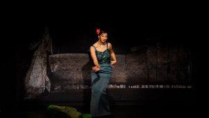 Eine junge Frau tanzt auf der Bühne. Sie trägt eine rote Blume in der Hochsteckfrisur und trägt ein grünes Abendkleid mit Pailletten.