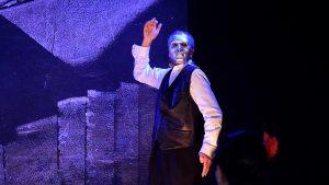 Ein Schauspieler mit einer silbernen Maske steht auf der bläulich beleuchteten Bühne. Er zeigt eine starke Gebärde: die rechte Hand schwebt über seinem Kopf und die linke deutet in den Boden.