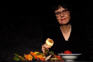Eine Schauspielerin sitzt an einem Tisch. Vor ihr liegen ein paar herbstliche Blätter und eine Schale mit Äpfeln steht auf dem Tisch. Sie trägt eine Brille und zeigt einen fragenden Blick. Sigrid Abendroth als Claudia in Der Tor und der Tod.