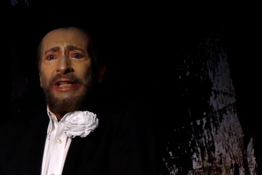 Ein Schauspieler mit stark geschminktem Gesicht zeigt einen betroffenen Ausdruck. Er trägt ein weißes Hemd eine dunkle Jacke und eine weiße Blume im Revier Wolfgang Keuter als Tod in Der Tor und der Tod.