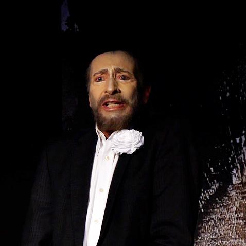 Ein Schauspieler in dunkler JAcke und weißem Hemd sieht beängstigt in die Kamera.