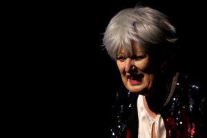 Eine Schauspielerin steht im schwarzen Bühnenraum. Sie trägt eine rot-schwarze Pailletten-Jacke. Sie hat weiße Haare in einem modernem Schnitt und schaut mit auf den Boden geneigtem Blick nachdenklich in die Welt. Doris Horn als Mutter in Der Tor und der Tod.