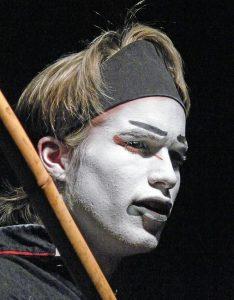 Florian Frowein als Hauptmann Fukakusa. Ein junger Mann mit blonden Haaren und verfremdeter Schminkmaske nach asiatischer Vorlage schaut ernst in den dunklen Bühnenraum. Er schultert eine Bambusstange.