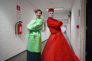 Eine junge Frau trägt eine grünern Trenchcoat. Neben ihr steht rechts ein Mann, ganzu in Rot gekleidet mit einem übergroßen Reifrock.