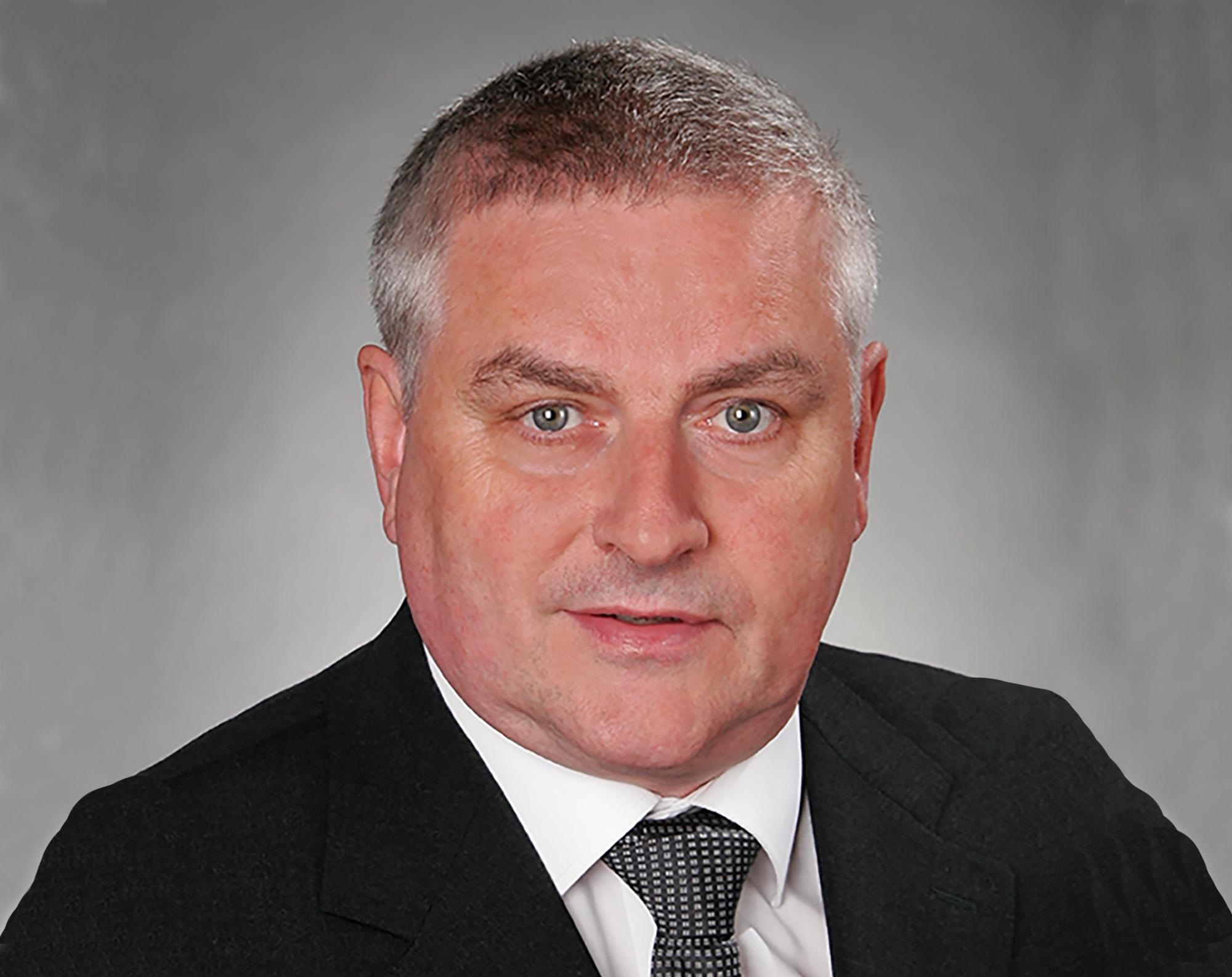 Portrait von Dr. J. Nelles. Er trägt ein weißes Hemd, eine dunkle 'KRawatte und ein dunkles Sakko. Er siehtr freundlich in die Kamera