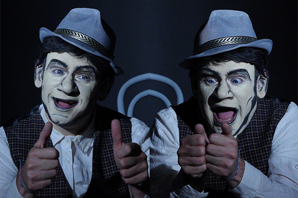 Kaspar. Er trägt einen grauen Hut uns ist geschminkt wie eine Comic-Figur.