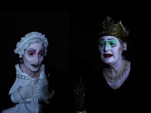 Theaterszene, links ist die Zofe mit einem Häubchen aus gesärkter Spitze und rechts eine Königin mit golderner Krone. Beide Figuren sund ganz weiß geschminkt, die Augen bei der Zofe sind rosa ud die beide Königing grün geschminkt.