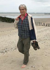 Michael geht barfuß am Strand spazieren. Er trägt ein kariertes Hemd, eine helle Jacke und eine olivgrüne Hose. Im Hintergrund ist das Meer zu sehen.