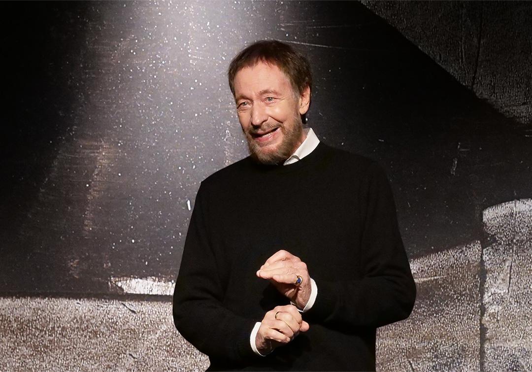 Wolfgang Keuter im Sprechtraining. Er trägt einen schwarzen Pilli und steht auf der Bühne.