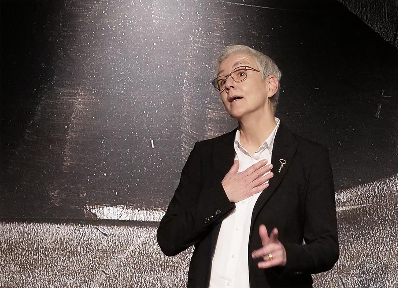Antje Orentat steht auf der Bühne. Sie trägt eine weiße Bluse und einen dunklen Blazer