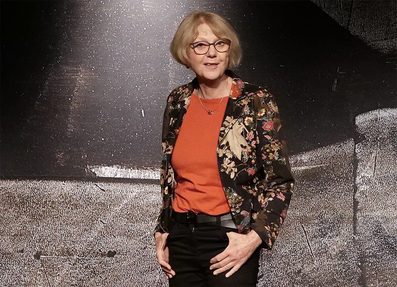 Sigrid Abendroth steht auf der Bühne. sie trägt eine orangefarbenes Shirt und draüber eine schwarzgrundige Jacke mit Blumenmuster