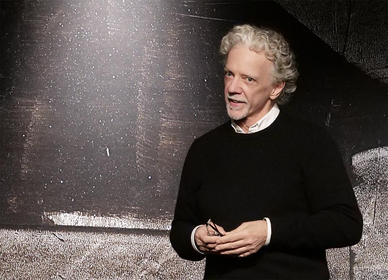 Gianni Sarto steht auf der Bühne. Er trägt ein weißes Hemd und einen schwarzen Pulli.