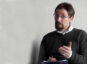 Wolfgang Keuter im Sprechtraining. Er sitzt auf einem Stuhl vor der weißen Wand des Seminarraums.