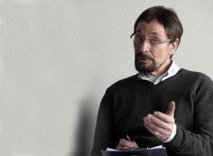 Wolfgang Keuter spricht über Slow Acting. Er sitzt auf einem Stuhl mit einem freundlichen, konzentriertem Gesichtsausdruck.
