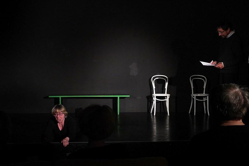 Vorne links liegt bäuchlinks eine Frau am Bühnenrand. Hinten rechts steht der Regiseur und erklärt sie Szene.