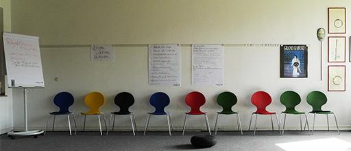 Im hellen Übungsraum steht eine Reihe bunter Stühle. Links ein Flipchart und vorne in der Mitte ein Meditationkissen auf dem Boden.