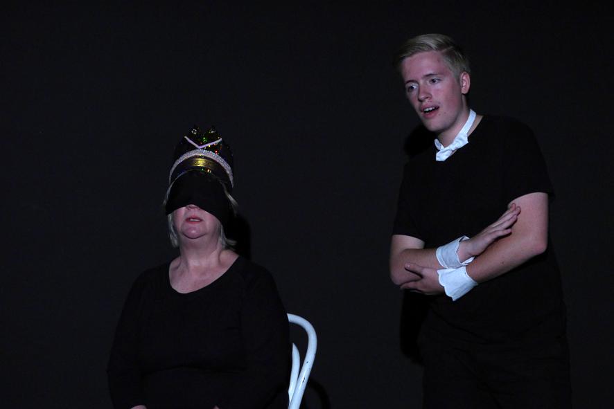 Eine Frau mit verbundenen Augen und ein Mann proben eine SZne im schwarzen Bühnenraum