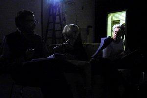 Im schwarzen Bühnenraum diskutieren die Spieler über den Text von Leonce und Lena. Im Hintgergrund die offene Tür.
