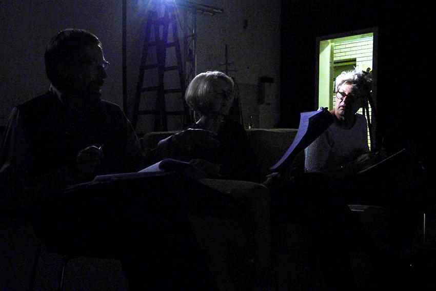 Im schwarzen Bühnenraum diskutieren die Spieler den Text. Im Hintgergrund die offene Tür.