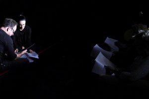 Im schwarzen Bühnenraum lesen die Spieler den Rollentext von Leonce und Lena. Zwei sitzen am Bühnenrand und drei auf Stühlen im Publikumsbereich