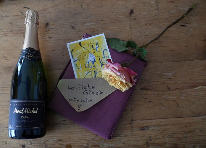 Auf einem Holztisch liegen ein Geschenk und eine Flasche Prosecco mit Glückwünschen