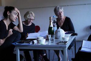Drei Spielerinnen sitzen am Tisch und diskutieren über den Rollentext.